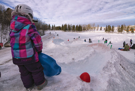 ALBERTA PARKS PHOTO - Maggie Swain gets ready for a run down the snow luge at Cypress Hills, which has no plans to ban tobagganing at the park and want families to enjoy the activity over the winter months. They are even planning on building a second snow luge.