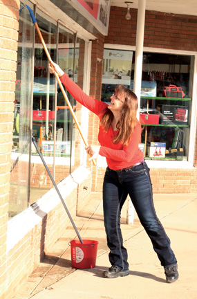 Donna Sadler washes the windows of the Bow Island Hardware store last week, taking advantage of the warm weather to get a little outside work done.