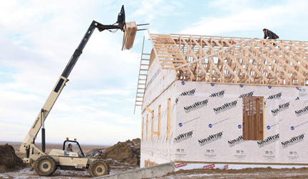 John Klassen lifts some trusses up to John Peters, who have both been working on the new 7,200-square foot Tween Valley Fellowship church being built on the west side of Bow Island.