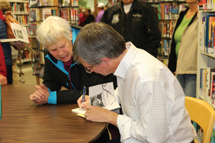Audrey Bereskowski gets her copy of the book autographed by Brett Loney.