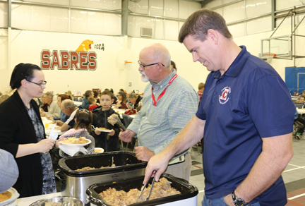 Cherry Coulee principal, Mike Daniels (front) and teacher, Craig Funston serve up supper at the school's fall fundraiser on Friday evening.