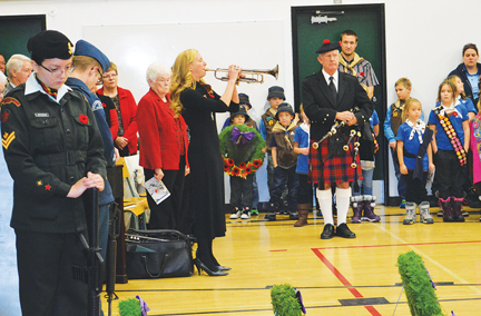 "Trumpeter Catherine Scott plays ""The Last Post"" while piper Eric Keane watches on."