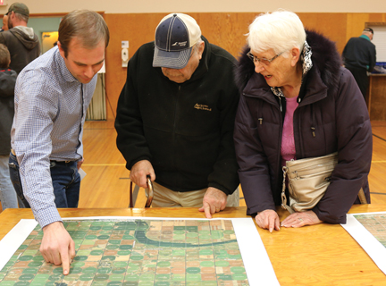 BluEarth Renewables representative, Jared Sproule shows county residents, Henry and Verna Willms the location on a map of one of the proposed projects.