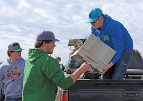 PHOTO BY JAMIE RIEGER- Kyle Crooymans, Mattias Crooymans, and Erik Bouw unload electronics at the landfill on Saturday.