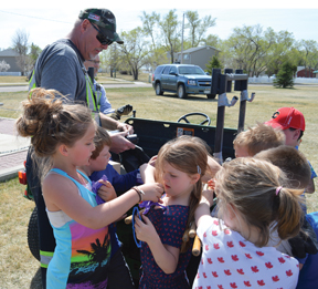 PHOTO BY TIM KALINOWSKI- CFB Suffield employee Cam Wiersma hands out rubber gloves and garbage bags to Ralston School students.
