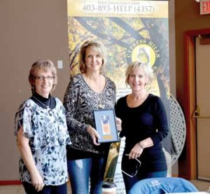 PHOTO BY TIM KALINOWSKI- Winter Fest chair Connie Matson (right) and Park Watch president, Darlene Ford (left) receive a bronze medal from Winter Games rep. Brenda Lee MacPhail.