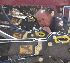 PHOTO BY JAMIE RIEGER- Brad Proud makes some adjustments to ensure the seed depth is correct for planting durum.