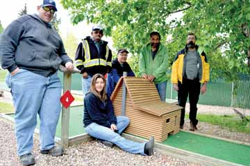 Photo by Tim Kalinowski- Venturers Society members (pictured, from left) Chuck McDonald, Sonia Gretchen, Brian Dodds, Paul Avery, Dwayne Mastel, and Bruce Wagner show off the replica of the old Cypress Hills NWMP barracks at the Lakeside Mini-Putt. The crew is going to be creating all new features for the putting holes, each based on a real Cypress Hills location, past or present.