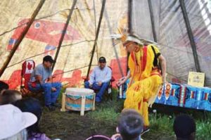 """PHOTO BY TIM KALINOWSKI- Ben Lloyd demonstrates a """"Grass Dance"""" for school kids while drummers, Readford Blackrider (right) and Shawn Redcrow lay down a beat. About 2,000 students visited the Elkwater Rodeo grounds last week to take in the four days of """"History of the Hills""""."""