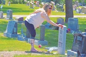 PHOTO BY TIM KALINOWSKI- Melissa Schaeffer places a poppy in memory of WW2 veteran Red Newnham, who passed away in 2015.