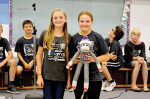 """Photo by Tim Kalinowski- Evi Neubauer (left) presents """"Thor the Monkey"""" to Jayla May to help raise awareness to the students' 1,000 T-shirts campaign."""