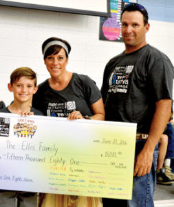 "Photo by Tim Kalinowski- The Seven Persons School Grade 5/6 class successfully sold 1,270 ""Team Tanya"" T-shirts and raised over $28,000 during the campaign. Pictured: Tanya and Tim Ellis accept a cheque from Rylan Dent for $15,081. The donation will help with Tanya's cancer fight."