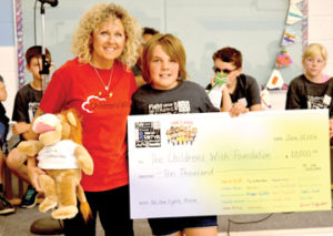 Photo by Tim Kalinowski- Donna Serr, president of the local Children's Wish Foundation, accepts a cheque from the student Cheyanne Zorn.