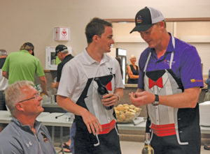 Photo by Jamie Rieger- Carson Cooper and Troy Loney serve up some wine at one of the VIP tables at the banquet.