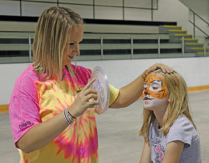 Photo by Jamie Rieger- Dawni Urlacher (left), from McMann Parent Link had a long line of young people waiting to get their faces painted after she was finished painting a tiger face on seven-year old Abigail Bailey.