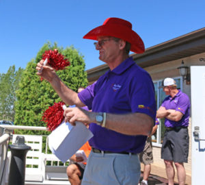 Photo by Jamie Rieger- Robin Knibbs gets out the pom-poms to encourage golfers to cheer in honour of Sue Andersen.