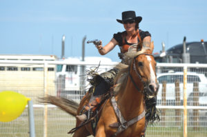 Photo by Tim Kalinowski- Competitive western-style mounted shooter Brit Debras demonstrates her dead-eye aim at the Ralston Rodeo on Saturday.