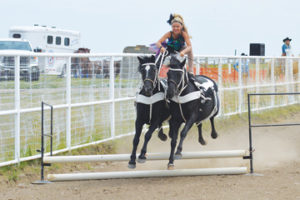 Photo by Tim Kalinowski- Cora Croteau of Young Gunz Trick Riders jumps her horses during the Roman riding demo.