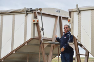 Photo by Tim Kalinowski- Charlie Redpath, project organizer, opens the tarp to receive the first load of grain.