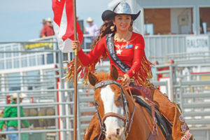 Photo by Tim Kalinowski- Medicine Hat Stampede Queen Brittney Chomistek rides in with the Canadian flag at the 37th annual Ralston Rodeo.
