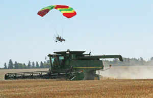 Photo By Jamie Rieger- Bert Schussler passes over this Shamrock Colony combine in his powered parachute.