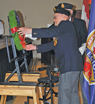 Photo by Jamie Rieger WWII veteran Ralph Lee (96 years old) places a wreath during the service in Foremost.