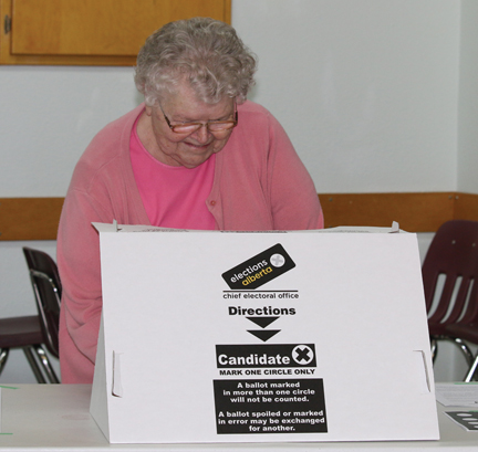 Margaret Reimer marks her ballot at the Bow Island polling station for advance voting on Friday afternoon.