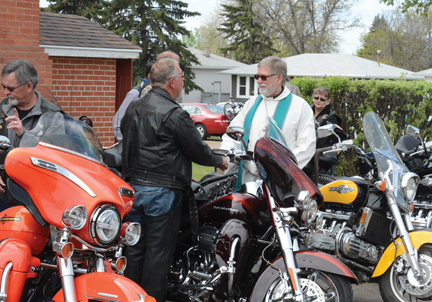 Gene Weber greets Rev. Blaine Schaufele at the Gordon Memorial United Church Blessing of the Bikes in Redcliff on Sunday. Oveer 100 riders and 80 bikes were blessed on Sunday to keep them safe on the road this summer.