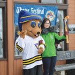 PHOTO BY TIM KALINOWSKI - Elkwater held its second annual Winter Festival on Saturday. Medicine Hat Alberta Winter Games mascot, Dusty and promotions committee member, Lee Krsilowez light up the torch to officially launch the Winter Games in SE Alberta.