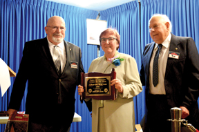 PHOTO BY TIM KALINOWSKI- Sharon Kirvan receives her plaque from Lions representatives, Brian Lowry and Vic Lutz.