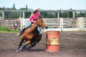 Photo by Tim Kalinowski- Brook Emard speeds through the barrel racing course at the Elkwater rodeo on Canada Day.