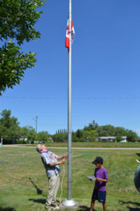Photo by Tim Kalinowski- Dave Dennis hoists the colours at a noon-hour Canada Day barbecue and flag-raising.