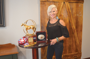 Photo by Tim Kalinowski- Lauren Boychuk shows off her trophy, ribbon, buckle, and other items she won as AQHA Boxing World Champion at her Medicine Hat home last week. Boychuk was also the overall cattle horse points leader in the AQHA last year.