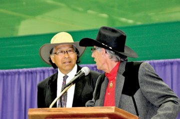 Photo by Tim Kalinowski- Stan Sakamoto (left) listens as President Norm Smith praises his 25 years of culinary service to the Stampede at the President's Luncheon Thursday.