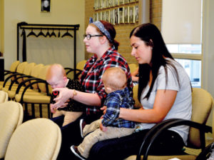 Photo by Tim Kalinowski- Sydney Page (left), with daughter Willow, and Alli Penner, with son, Gavin, sit in on the county meeting.